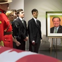 Ontario MPP Christine Elliott and her sons stand by the casket of her husband, the late former federal finance minister Jim Flaherty, during visitation in Whitby, Ont., on Tuesday, April 15, 2014. THE CANADIAN PRESS/Frank Gunn