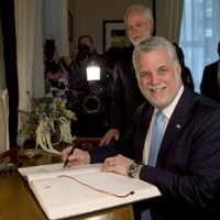 Quebec Premier Philippe Couillard signs a document during his official visit with Lt. Governor Pierre Duchesne, behind, Wednesday, April 23, 2014 at the Lt. Governor's office in Quebec City. THE CANADIAN PRESS/Jacques Boissinot