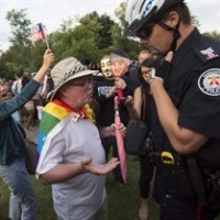 Rob Ford supporters jeer as a LGBT-rights supporter speaks to a police officer after claiming he was assaulted at Ford Fest in Toronto on Friday, July 25, 2014. THE CANADIAN PRESS/Darren Calabrese