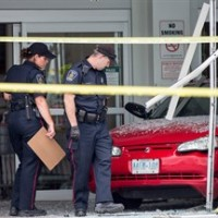 Police investigate after a car backed through the entrance of Costco in London, Ont., on Friday, July 25, 2014. A six-year-old child who was injured after being hit by a car that crashed through the front doors of the store has died. THE CANADIAN PRESS/ Geoff Robins