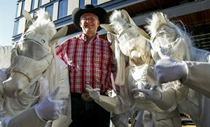 Prime Minister Stephen Harper poses with people dressed as horses at the Calgary Stampede parade, Friday, July 4, 2014. THE CANADIAN PRESS/Jeff McIntosh