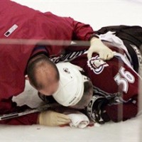 Colorado Avalanche forward Steve Moore is attended to by the team trainer after being injured in a fight with Vancouver Canucks Todd Bertuzzi during the third period of NHL action in Vancouver, B.C., Monday, March 8, 2004. A settlement has been reached in Moore's lawsuit against former Vancouver Canucks forward Bertuzzi for his NHL career-ending attack. A lawyer for Bertuzzi confirmed the settlement but says the terms are confidential. THE CANADIAN PRESS/Chuck Stoody