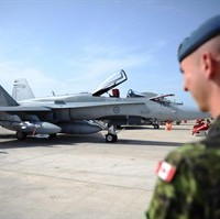A Canadian soldier looks at a CF-18 as it at Camp Fortin in Trapani, Italy, on September 1, 2011. THE CANADIAN PRESS/Sean Kilpatrick