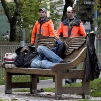 Park rangers walk past a homeless person sleeping on a bench in Oppenheimer Park in downtown Vancouver, on Oct. 16, 2014. THE CANADIAN PRESS/Jonathan Hayward