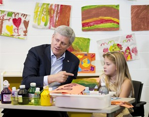 Prime Minister Stephen Harper does arts and crafts with a student at the Joseph and Wolf Lebovic Jewish Community Campus in Vaughan, Ont., on Wednesday, October 30, 2014. THE CANADIAN PRESS/Nathan Denette