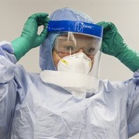A healthcare professional adjusts her mask during a demonstration of Personal Protective Equipment (PPE) procedures at Toronto Western Hospital on Friday October 17, 2014. A man who recently travelled to Sierra Leone walked into a southern Ontario hospital last week, feeling unwell. Four minutes later, he was in quarantine and being tested for the Ebola virus. Those tests proved negative.Suppose they'd been positive. What would happen next? THE CANADIAN PRESS/Chris Young