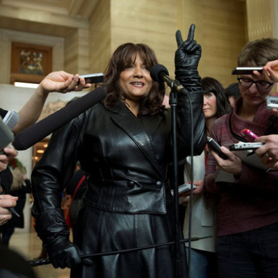 Terri-Jean Bedford flashes a victory sign as she speaks with the media after learning Canada's highest court struck down the country's prostitution laws at the Supreme Court of Canada in Ottawa Friday December 20, 2013. THE CANADIAN PRESS/Adrian Wyld