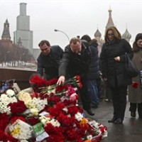 People lays flowers at the place where Boris Nemtsov, a charismatic Russian opposition leader and sharp critic of President Vladimir Putin, was attacked, at Red Square in Moscow, Russia, Saturday, Feb. 28, 2015. Nemtsov was gunned down Saturday near the Kremlin, just a day before a planned protest against the government. (AP Photo/Denis Tyrin)