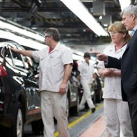 Prime Minister Stephen Harper, centre, and Labour Minister Kellie Leitch (right) talk with Honda production associate Rhonda St. Pierre, left, as they look at the assembly line at Honda of Canada Manufacturing Plant 2 in Alliston, Ont., on Monday, March 30, 2015. THE CANADIAN PRESS/Nathan Denette
