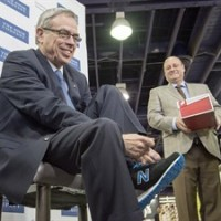 Federal Finance Minister Joe Oliver tries on his new budget shoes with the assistance of Bruce Dinan, president of Town Shoes, during a photo op in Toronto on Monday, April 20, 2015. THE CANADIAN PRESS/Frank Gunn