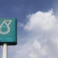 A man works on a signage bearing a Petronas logo in Kuala Lumpur