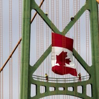 Workers install the Canadian flag on the Angus L. Macdonald Bridge in preparation for Canada Day on Tuesday, June 30, 2015. The bridge is one of two suspension bridges linking the Halifax Peninsula to Dartmouth. THE CANADIAN PRESS/Andrew Vaughan
