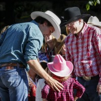 Prime Minister Stephen Harper, right, meets Liberal leader Justin Trudeau, left, and his daughter Ella-Grace while attending the Calgary Stampede parade, Friday, July 4, 2014. THE CANADIAN PRESS/Jeff McIntosh