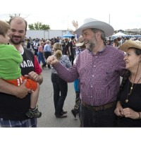 Elijah Day, 3, being held by father Rod Day, left, shyly avoids a fist pump with NDP Leader Thomas Mulcair, second from right, and wife Catherine during a Stampede breakfast in Calgary, Alberta on Saturday, July 4 , 2015. THE CANADIAN PRESS/Larry MacDougal