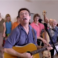 Ottawa folksinger Tony Turner wrote and performed the song Harperman with help from Ann Downey on bass and the Crowd of Well Wishers choir, June 12, 2015 (screen capture from video)