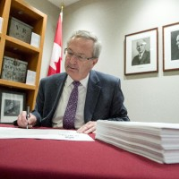 Chief Electoral Officer Marc Mayrand signs the writs of election for the 42nd general election during a photo op in Gatineau, Que., on Friday, August 14, 2015. There are a total of 338 writs, one for each of the electoral districts. THE CANADIAN PRESS/Justin Tang
