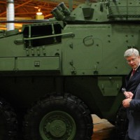 Prime Minister Stephen Harper tours the General Dynamics Land Systems - Canada plant, next to a LAV 6.0 (Light Armoured Vehicle) being built for Canada, at the facility in London, Ont., Friday, May 2, 2014. THE CANADIAN PRESS/Dave Chidley