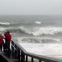 People watch the waves in a rainstorm at Atlantic Ocean at Carolina Beach, N. C., Friday, Oct. 2, 2015. Millions along the East Coast breathed a little easier Friday after forecasters said Hurricane Joaquin would probably veer out to sea instead of joining up with a drenching rainstorm that is bringing severe flooding to parts of the Atlantic Seaboard. (AP Photo/Harry Hamburg)