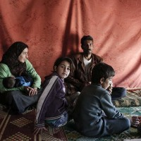The Al Bazazi family from the Babr Amr district of Homs – one of the most restive areas of Syria in the early days of the conflict – sit in the tent that is now their home in a refugee camp in Lebanon's Bekaa Valley, on November 27, 2015. The Al Bazazi family are hoping to soon be resettled in Canada. (Photograph by Sam Tarling)