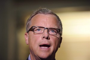Saskatchewan Premier Brad Wall speaks at the Saskatchewan Legislative Building in Regina, Sask., Friday, July 24, 2015. Wall wants the federal government to suspend its plan to bring in 25,000 Syrian refugees by the end of the year. THE CANADIAN PRESS/Mark Taylor