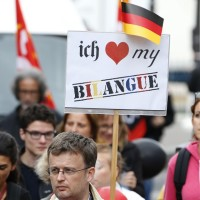 """A striking teacher holds up a placards which reads """"I love my bilingual classroom"""" as he takes part in a nation-wide protest against new measures aimed at revamping the country's school system in Paris, France, September 17, 2015. French teachers are opposed to the reform, their unions say, fearing it will increase competition between schools and so exacerbate inequalities.   REUTERS/Charles Platiau - RTS1L02"""