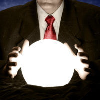 A businessman is consulting a crystal ball to foretell the future.