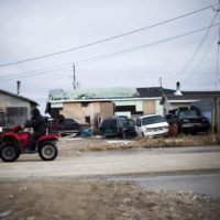 A man rides his ATV in the northern Ontario First Nations reserve in Attawapiskat, Ont., on Tuesday, April 19, 2016. In many ways, Attawapiskat - population 2,100 - has all the trappings of any small town, including older folk lamenting the changing of the times. THE CANADIAN PRESS/Nathan Denette ORG XMIT: CPT106