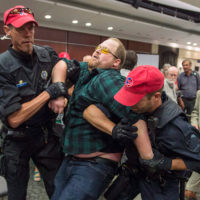 A demonstrator is taken away by police officers after disrupting the National Energy Board public hearing into the proposed $15.7-billion Energy East pipeline project proposed by TransCanada Monday, August 29, 2016 in Montreal. (Paul Chiasson/CP)