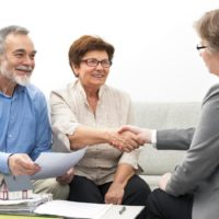 Seniors ouple meeting with financial adviser, handshake