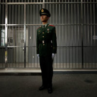 Local Input~ A paramilitary guard stands before the bars of a main gate to the No.1 Detention Center during a government guided tour in Beijing on October 25, 2012. The rare visit to the facility, which has capacity for 1,000 inmates, was opened to the foreign media as Beijing prepares for the 18th Congress of the Communist Party of China.      AFP PHOTO / Ed Jones        (Photo credit should read Ed Jones/AFP/Getty Images)  0623 ed glavin