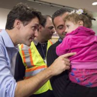 Canadian Prime Minister Justin Trudeau greets 16-month-old Madeleine Jamkossian, right, and her father Kevork Jamkossian, refugees fleeing the Syrian civil war, during their arrival at Pearson International airport, in Toronto, on Friday, Dec. 11, 2015. THE CANADIAN PRESS/Nathan Denette