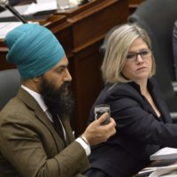 Ontario NDP Leader Andrea Horwath, right, talks with MPP Jagmeet Singh as Ontario Finance Minister Charles Sousa delivers the Ontario 2016 budget at Queen's Park in Toronto on Thursday, February 25, 2016. THE CANADIAN PRESS/Nathan Denette